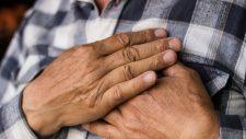 medical alert system mans hands holding heart