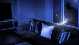 burglar looking through a residential window at night