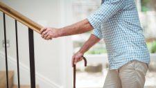 senior adult walking up stairs with lifegard medical alert