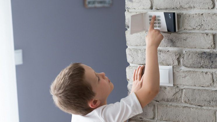 child using home security system keypad