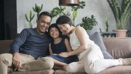 smiling family sitting on couch protected by their home security system