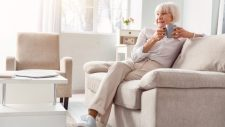 elderly woman sitting on sofa secure because of her wireless home security system
