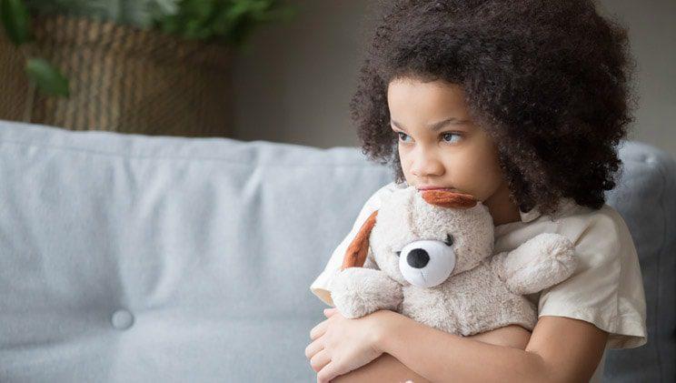 little girl sitting on sofa while holding stuffed bear