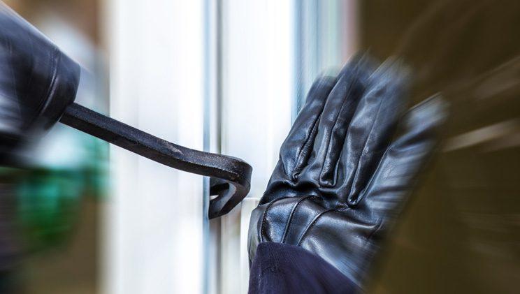 burglar hands prying open a door