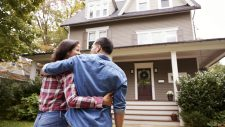 new homeowner couple standing in front of house