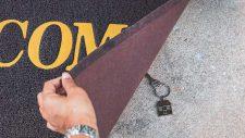mans hand hiding house keys under front door mat